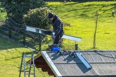 默尔斯,德国- 2018年2月05日:平衡在有金属面对的屋顶的盖屋顶的人 免版税图库摄影