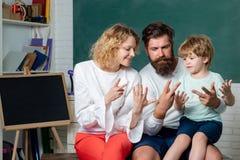 鼓励他们的小儿子的父母在第一天学校前 年轻幸福家庭教育的算术一起 ?? 图库摄影