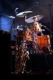 鼓成套工具和saxofone在夜场面 免版税库存图片