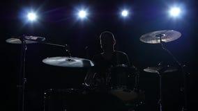 鼓手播放在鼓的曲调精力充沛地 黑色背景 回到光 剪影 慢的行动 股票视频