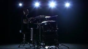 鼓手播放在鼓的曲调精力充沛地 黑色背景 回到光 剪影 股票录像