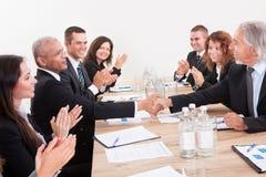 鼓掌企业的小组坐在表和 免版税库存图片