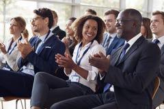 鼓掌在企业研讨会的微笑的观众 免版税库存照片