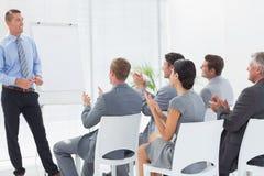 鼓掌在会议期间的微笑的企业队 免版税库存照片