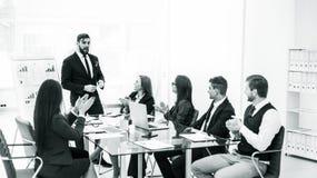 鼓掌对在新的项目的介绍的经理财务的企业队在工作场所 免版税图库摄影