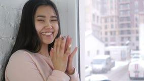 鼓掌年轻亚裔的妇女,拍手,坐在窗口 股票录像