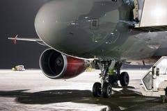 鼻子、乘客飞机引擎和起落架在夜机场围裙的 免版税图库摄影