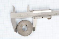 齿轮和轮尺在座标图纸 库存照片