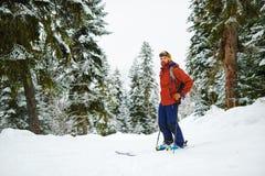 齿轮的人滑雪者在一块沼地站立在森林里 图库摄影