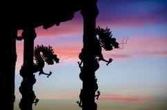 龙与好的暮色天空的雕象剪影 免版税库存照片