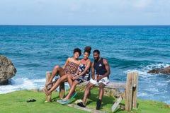 龙湾,波特兰,牙买加- 2017年11月22日:美国millennials开心的一个小组在海岸线在龙湾, 免版税库存照片