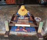龙目岛,印度尼西亚-大约2015年:回教妇女编织一套服装使用一台传统编织机在一个村庄在龙目岛,印度尼西亚 库存照片