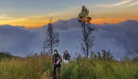龙目岛,印度尼西亚2015年6月:走沿供徒步旅行的小道的远足者在日落到达Mt Rinjani火山的火山口,在它得到黑暗前 图库摄影