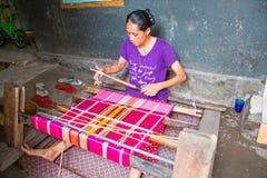 龙目岛,印度尼西亚- 2016年12月30日:编织在一台织布机的妇女在印度尼西亚 库存照片