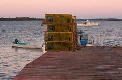 龙虾陷井和小船在日出 免版税库存照片