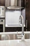 龙头和水槽在现代厨房里 免版税库存照片