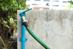 龙头和绿色水水管 免版税库存图片