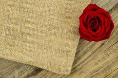 黄麻,与玫瑰色花的粗麻布纹理在老木桌上 免版税库存照片