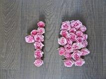 10,十-桃红色玫瑰的葡萄酒数字在黑暗的木头背景的  图库摄影