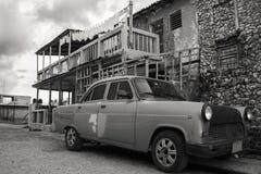 20/03/2015,哈瓦那,古巴:一辆老complety习惯被装配的汽车在一个老古巴大厦前面生锈  图库摄影