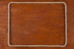 绳索,在木表面的背景的谎言框架  免版税库存照片