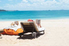 读,当晒日光浴在海滩时的人夫妇  图库摄影