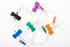 黑,橙色,绿色,蓝色和紫色有针的蝴蝶塑料导尿管由保护罩关闭了 免版税库存图片