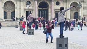 巴黎,法国- 2016年12月, 31日 摆在和做照片的不同种族的游人在天窗,著名法国博物馆附近 免版税图库摄影