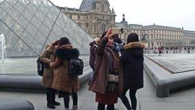 巴黎,法国- 2016年12月, 31日 摆在和做照片的女性亚裔游人在天窗,著名法国博物馆附近 库存照片