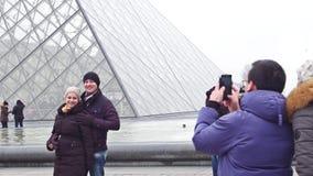 巴黎,法国- 2016年12月, 31日 摆在天窗,著名法国博物馆和普遍旅游附近的愉快的夫妇 免版税库存图片