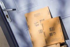 巴黎,法国- 2017年2月08日:亚马逊填装在前面的小包包裹房子的门 亚马逊,是美国电子com 免版税库存图片