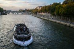 巴黎,法国- 2014年10月11日:巡航在塞纳河的典型的旅游船`平底船Mouche `,在新桥下,在Ile de la Ci附近 库存照片
