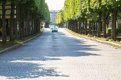 巴黎,法国- 2014年7月14日:有n的大被铺的沿途有树的路 免版税图库摄影