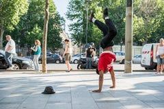 巴黎,法国2012年5月25日:现代舞蹈家在爱丽舍,法国街道上的胳膊做平衡  都市的生活方式 H 免版税库存照片