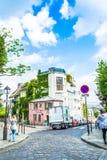 巴黎,法国- 2015年5月27日:街道在巴黎在蒙马特地区在与绿色树和蓝天的一个晴天 库存图片