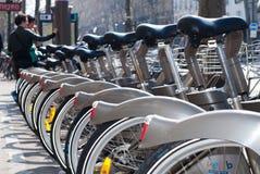 巴黎,法国- 2009年4月02日:预留他们的自行车的两个人在Velib驻地公开自行车租务在巴黎 Velib有hig 免版税库存照片