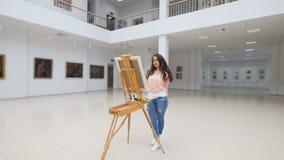 画廊,站立在空白的帆布前面的女孩 股票录像
