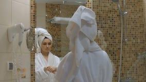 年轻,美丽的妇女在卫生间里应用面霜 股票视频