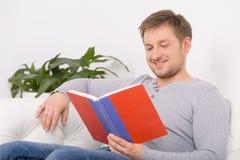 年轻,英俊的人阅读书特写镜头画象  库存图片