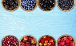 黑,蓝色和红色莓果 黑莓,蓝莓,无核小葡萄干,蓝莓,草莓,石榴,在一把木弓的樱桃 图库摄影