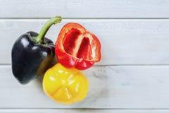 黑,黄色辣椒粉和裁减红色辣椒粉在一个白色木板 图库摄影