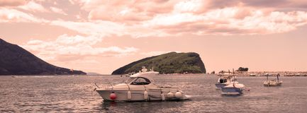 :反对背景圣尼古拉海岛的停住的汽艇在黎明 库存照片