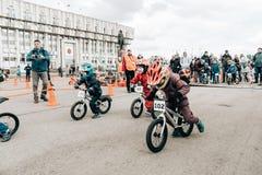 :孩子的非职业竞争平衡在列宁广场的自行车 库存图片