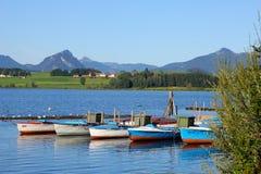 :湖Hopfensee有Allgau和提洛尔阿尔卑斯的风景看法 库存图片