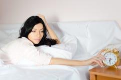 6 30 :说谎在床上的美丽的华美的深色的少妇关闭金闹钟画象图片 库存照片