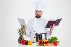 ?强麦酒厨师厨师拿着桌计算机的和食谱预定 库存照片