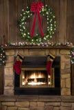 Δάπεδο τζακιού εστιών Χριστουγέννων με το στεφάνι και τις γυναικείες κάλτσες Στοκ Εικόνα