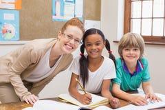Δάσκαλος και μαθητές που εργάζονται στο γραφείο από κοινού Στοκ Εικόνες