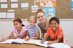 Δάσκαλος και μαθητές που εργάζονται στο γραφείο από κοινού Στοκ Φωτογραφία
