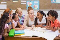 Δάσκαλος και μαθητές που εργάζονται στο γραφείο από κοινού Στοκ Εικόνα